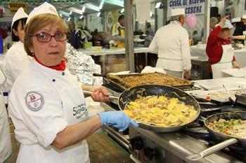 Una cuoca che prepara le pietanze alla Sagra della Seppia